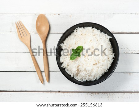 bowl full of rice and spoon on white wood - stock photo