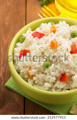 bowl full of rice isolated on wooden background - stock photo