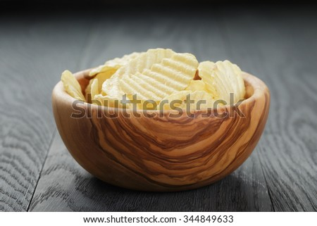 bowl full of salted potato ships on old wooden table, selective focus - stock photo