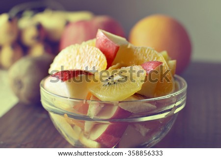 Bowl of assorted fresh fruits : Apple, oranges, kiwi and banana in a glass bowl on a wooden table. Image is treated with vintage effect for background purposes.  - stock photo