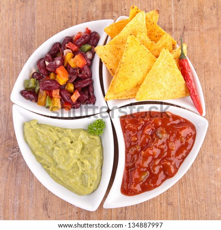 bowl of assortment of dips and tortilla chips - stock photo