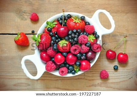 Bowl of berries and cherry  - stock photo