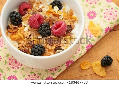 Bowl of breakfast healthy muesli and corn flakes with berries. - stock photo