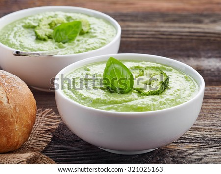 bowl of broccoli and green peas cream soup on wooden table - stock photo