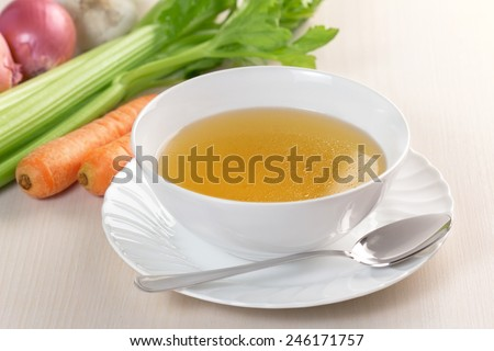 bowl of broth and fresh vegetables on wooden table - stock photo