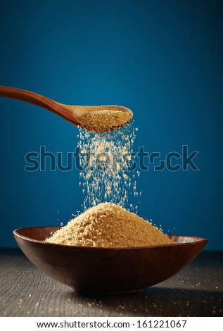 bowl of brown sugar and wooden spoon - stock photo