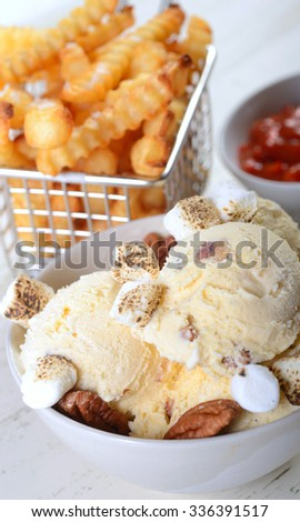 Bowl of Butter Pecan Ice Cream with whole pecans, toasted marshmallows with crispy French Fries and a red pepper aoli ketchup - stock photo