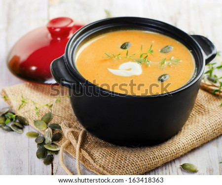 Bowl of Butternut Squash Soup  on wooden table. Selective focus - stock photo
