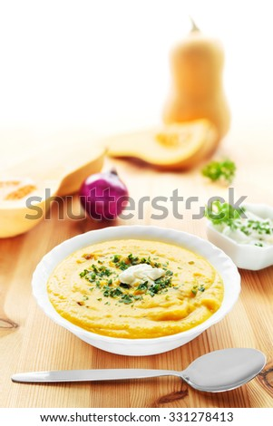 Bowl of butternut squash soup with spoon and squashes - stock photo