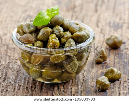 bowl of capers on wooden table - stock photo
