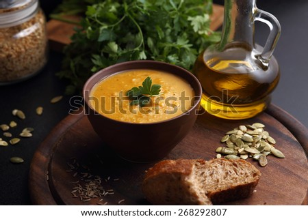 Bowl of carrot and pumpkin soup, bottle of olive oil, bread and green on the wooden board - stock photo