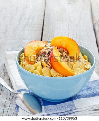 Bowl of cereal with muesli and fresh peach - stock photo