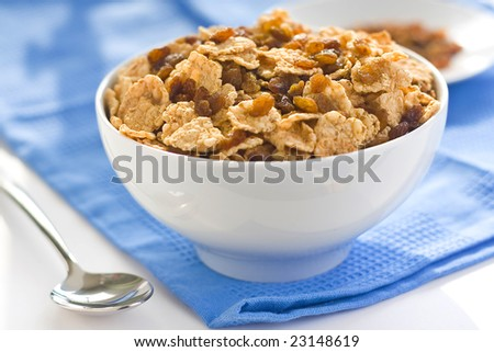 bowl of cereal with raisins, milk and orange juice - stock photo