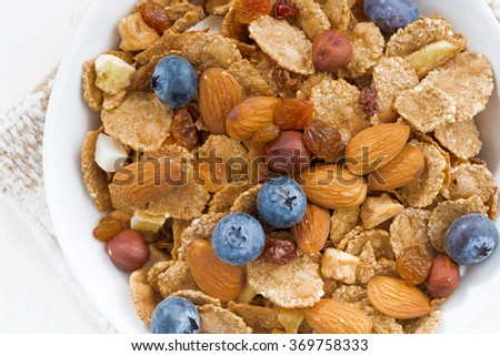 bowl of cereals flakes, blueberries and nuts, closeup top view, horizontal - stock photo