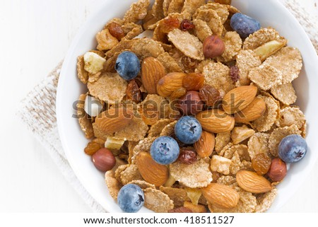 bowl of cereals flakes, blueberries and nuts on white table, top view, horizontal - stock photo