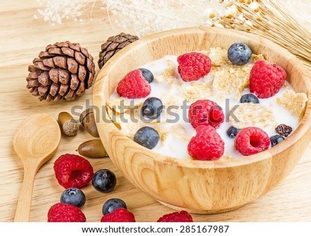 Bowl of cereals with raspberries and blueberrys on a wooden table, healthy breakfast. - stock photo