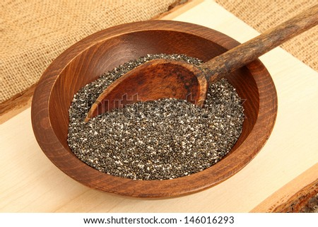 Bowl of Chia Seeds With Spoon On Wooden Plank - stock photo