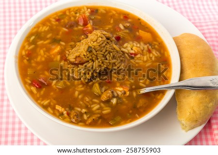 Bowl of chicken and sausage gumbo with large scoop of dirty rice and pone of sour dough bread on pink gingham.  Overhead View. - stock photo