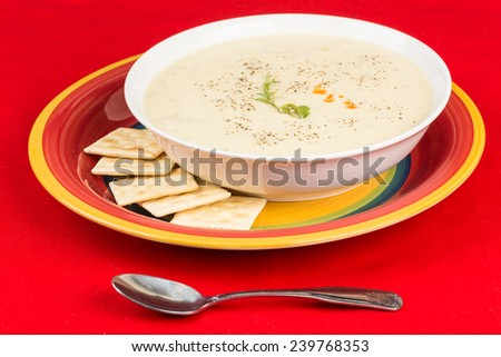 Bowl of Chicken Corn Chowder with saltine crackers in bright red setting.  Green garnish and dash of hot sauce. - stock photo