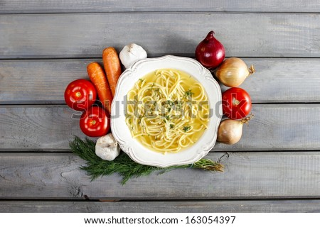 Bowl of chicken soup with noodle. Fresh, raw vegetables around. Top view, copy space. - stock photo