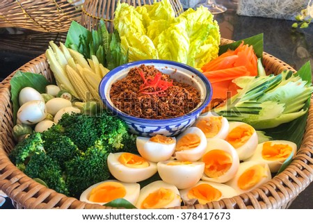 Bowl of Chili Paste with Various Type of Fresh Vegetables and Eggs in Big Rattan Basket for Traditional Thai Style Healthy Meal - stock photo