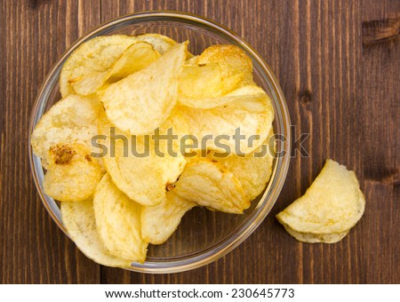 Bowl of chips on wooden table top view - stock photo