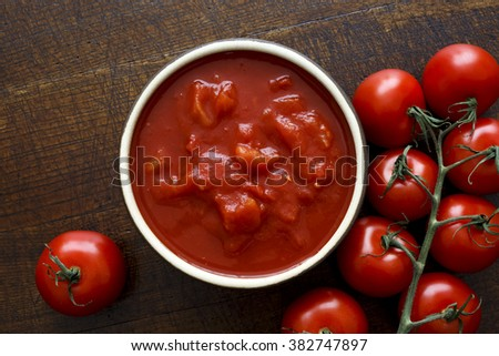 Bowl of chopped tomatoes isolated on rustic dark wood surface from above. Next to fresh whole tomatoes. - stock photo