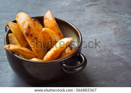 Bowl of chunky potato wedges fries served on a rustic stone, slate, gray table top. - stock photo