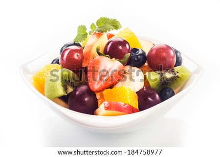 Bowl of colorful tropical fruit salad with fresh ripe strawberries, grapes, kiwifruit, orange and apple garnished with a sprig of peppermint on a white background - stock photo