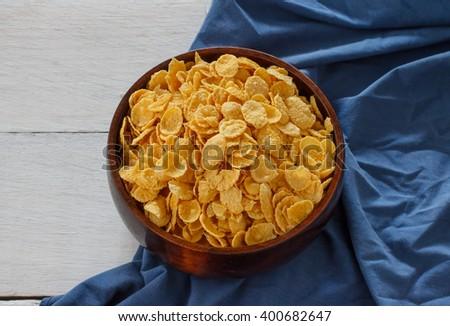 bowl of cornflakes put on white wood with dark blue napkin. - stock photo