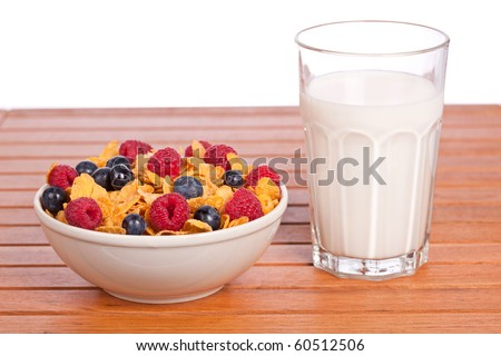 Bowl of cornflakes with fruits and a milk tumbler on white background. Shallow depth of field - stock photo