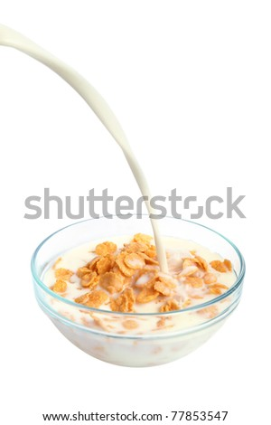 Bowl of cornflakes with pouring milk on white background - stock photo