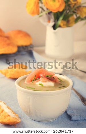 Bowl of creamy leek soup with smoked salmon and cream cheese. Retro style toned.  - stock photo