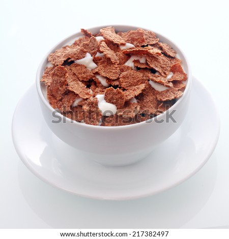 Bowl of crispy flakes of chocolate flavored breakfast cereal in milk for a tasty nutritional meal served in a white ceramic bowl and saucer , in square format - stock photo