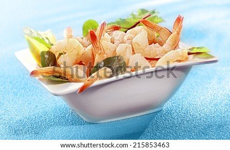 Bowl of delicious grilled prawn or shrimp tails garnished with fresh lemon and baby spinach on a colorful turquoise blue background - stock photo