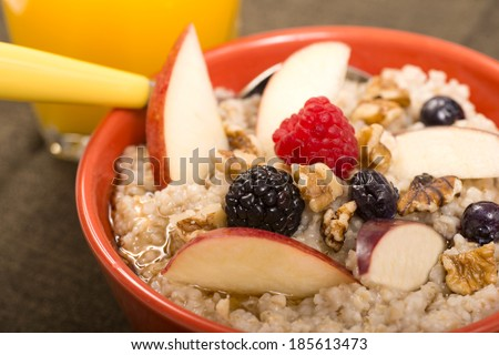 Bowl of delicious steel cut oats with fresh fruit, honey and orange juice - stock photo