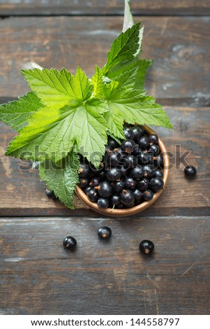 Bowl of fresh black currants on wooden table - stock photo