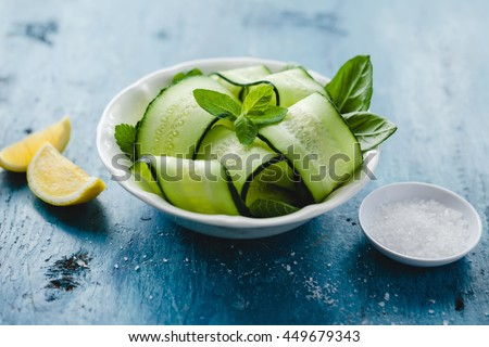 Bowl of fresh cucumber and mint salad with sea salt and lemon - stock photo