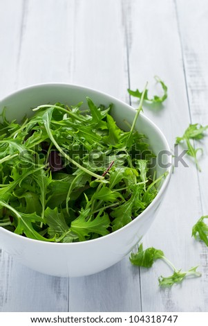 Bowl of fresh green salad on a white table - stock photo