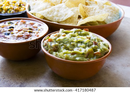 Bowl of fresh guacamole, with chips and salsa ready to eat. - stock photo
