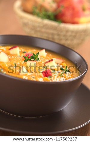 Bowl of fresh homemade sweet potato and apple soup with thyme (Selective Focus, Focus in the middle of the soup) - stock photo