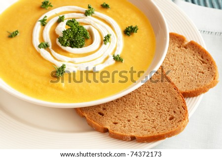 Bowl of fresh hot butternut soup with cream and parsley, served with rye berliner bread - stock photo