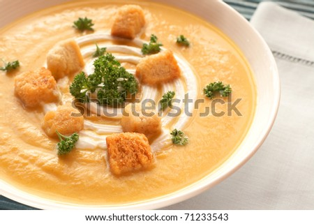 Bowl of fresh hot butternut soup with cream, parsley and croutons - stock photo