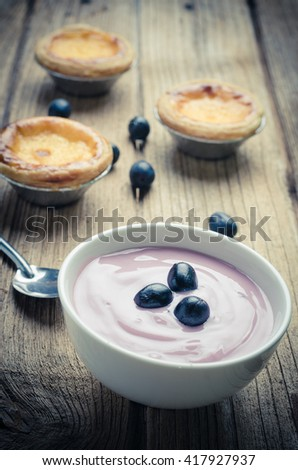 Bowl of fresh mixed berries and yogurt with farm fresh strawberries, blackberries and blueberries served on a wooden table - stock photo