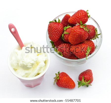 Bowl of fresh organic red strawberries with whipped cream - stock photo