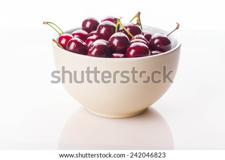 Bowl of fresh red cherries on white background - stock photo