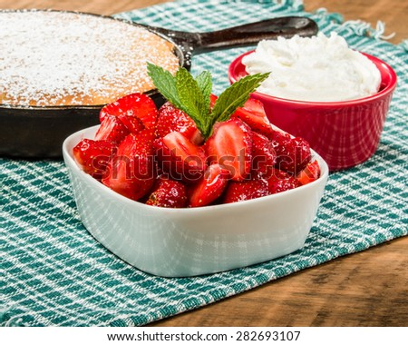 Bowl of fresh red strawberries with skillet cake - stock photo