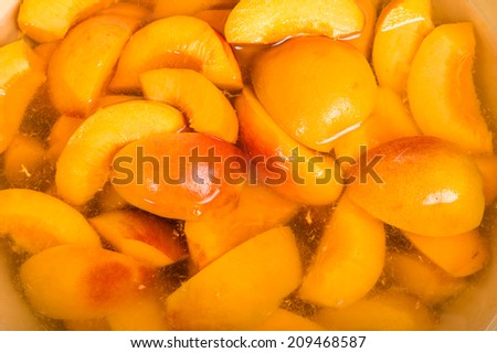 Bowl of fresh sliced yellow peaches in a bowl of clear syrup - stock photo