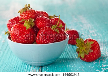 Bowl of fresh strawberries on blue wooden background - stock photo