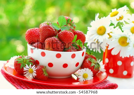 bowl of fresh strawberries on table in the garden - stock photo